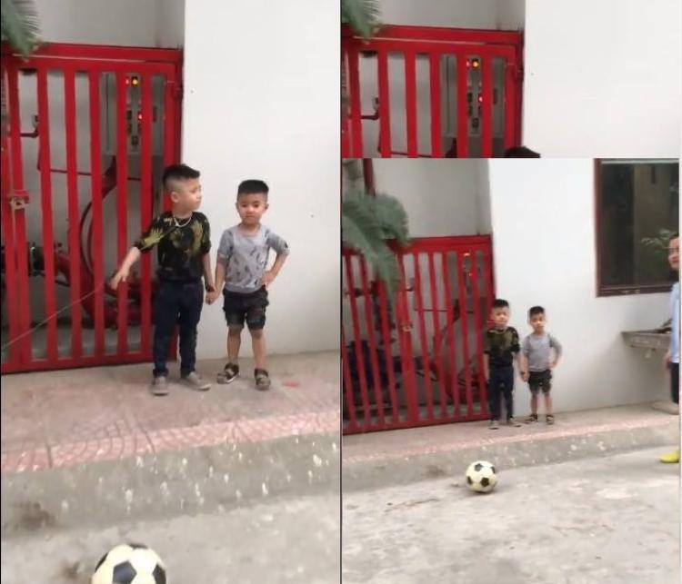 Cậu bé khá căng thẳng, liên tục nắm tay em trai đứng bên.