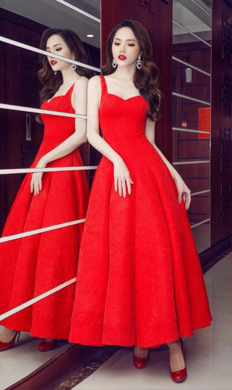 """Chẳng cần đính kết cầu kỳ, chiếc váy xòe hai dây với tông màu đỏ đã giúp Hương Giang tỏa sáng khi tôn lên làn da trắng của người đẹp, kết hợp với kiểu tóc xoăn sóng, Hoa hậu Chuyển giới vô cùng quyến rũ khiến """"gái thẳng"""" còn phải thầm ghen tỵ."""