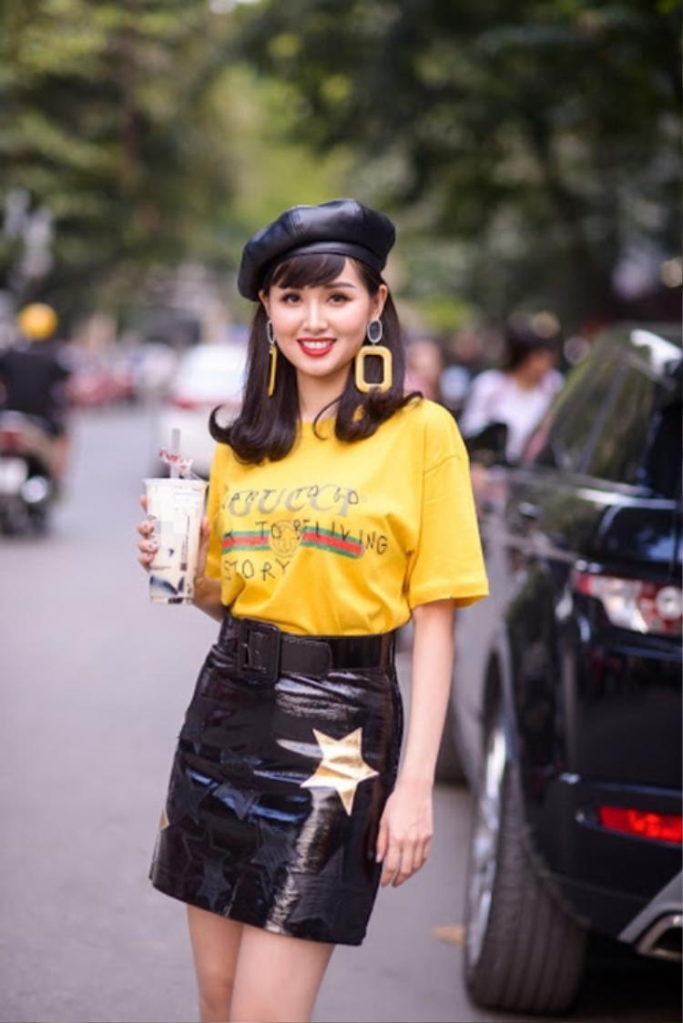 """Tâm Tít cũng sở hữu một phiên bản màu vàng. Thiết kế được cựu hot girls phối khá bắt mắt với chân váy da bóng, mũ nồi kiểu cách, hoa tai to bản,… tạo nên tổng thể sành điệu, trẻ trung. Ngoài các mỹ nhân kể trên, còn khá nhiều những tín đồ thời trang, hot girls trong showbiz Việt ưu ái thiết kế của """"ông lớn"""" làng mốt thế giới."""