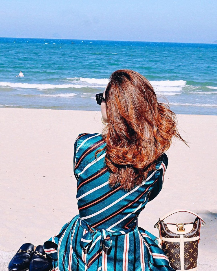 """Thay vì xúng xính váy áo dự sự kiện như các người đẹp khác, Minh Hằng lại dành cho mình một ngày nghỉ ngơi bên bãi biển. Cô nàng diện váy sọc tông màu xanh, đeo kính mát, hai bên không quên để thêm đôi giày Gucci và túi Louis Vuitton đắt giá, nhằm tăng độ """"xịn sò"""" cho tấm ảnh."""