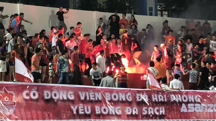 Hình ảnh đối nghịch từ thông điệp của tấm băng rôn và cảnh CĐV Hải Phòng đốt pháo sáng.