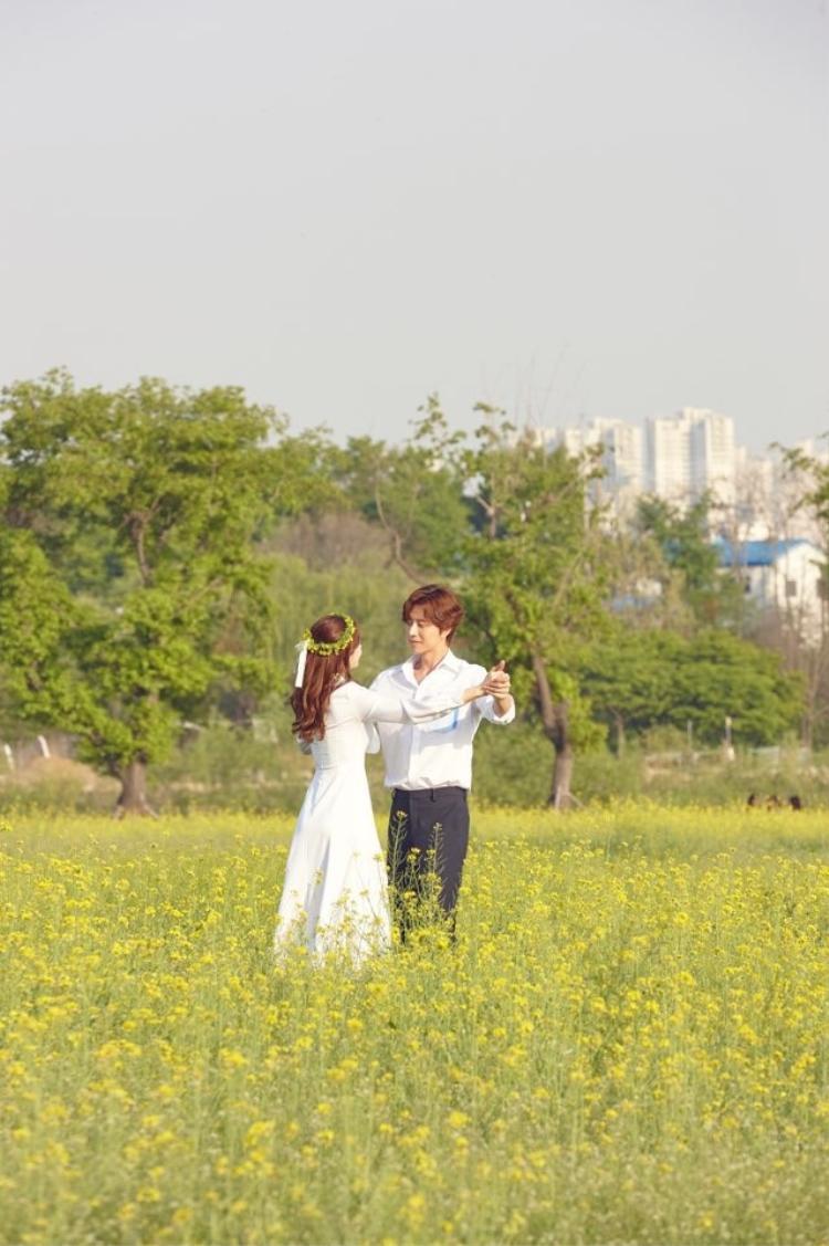 """Nana mặc một bộ váy dài màu trắng tinh khôi kèm theo một vòng hoa được đặt trên đầu, trong khi Park Hae Jin như """"soái ca"""" từ truyện ngôn tình bước ra, anh mặc quần tây cùng áo sơ mi trắng. Cả hai cùng trao nhau ánh mắt trìu mến, nắm tay và khiêu vũ."""