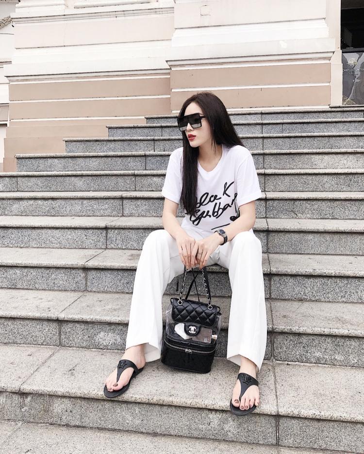 """Dù đang bận rộn tham gia chương trình truyền hình thực tế """"Khi đàn ông mang bầu"""", Kỳ Duyên vẫn không quên ăn mặc cực chất. Nàng hậu lựa chọn set đồ thời thượng """"đắt xắt ra miếng"""" toàn tông trắng khi xuống phố, gồm áo phông Dolce & Gabbana, dép Versace, túi Chanel và kính mát Yves Saint Laurent."""