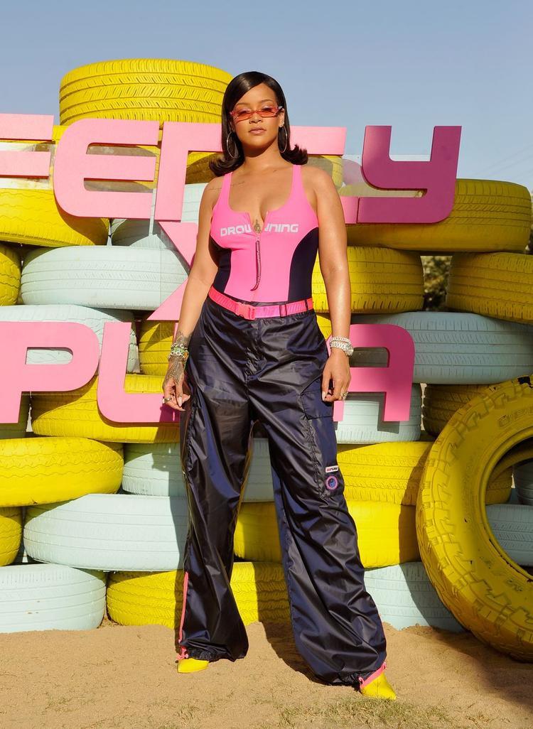 Xuất hiện trong lễ hội hòa nhạc với qui mô lớn nhất nhì thế giới Coachella, Rihanna khiến khán giả thích thú với gu thời trang mới lạ. Cô khéo léo kết hợp áo bơi với quần thể thao form rộng thùng thình. Tổng thể được làm nổi bật bởi chiếc kính râm màu sắc sặc sỡ, giày cao gót màu vàng chanh là điểm nhấn của cả trang phục. Được biết, đây là một bộ sưu tập mới của Fenty X Rihanna.