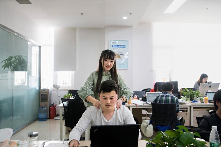"""Shen Yue, một cô gái 25 tuổi có bằng xây dựng dân dụng, mát-xa cho một nhân viên nam tại Chainfin.com. Cô làm việc như một người """"tạo động lực"""" tại đây."""