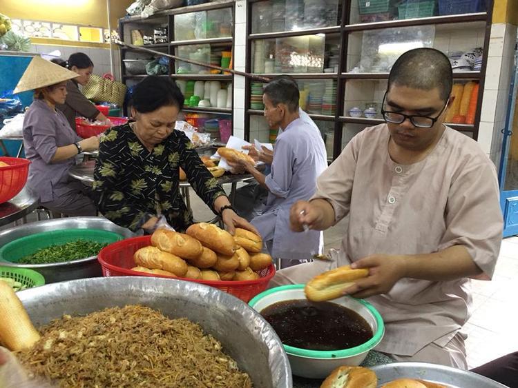 Các tăng ni, phật tử trong chùa đang chuẩn bị các phần bánh mỳ chay để kịp giờ đưa đến các điểm từ thiện.