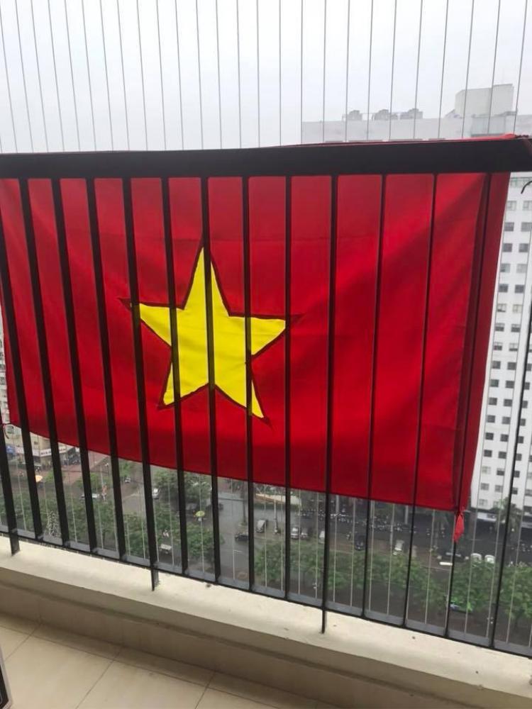 Một cư dân chụp lại ảnh quốc kỳ từ ban công của mình. Ảnh: Nguyễn Jess