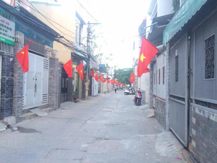 Nhà phố cũng phấp phới sắc cờ tung bay.