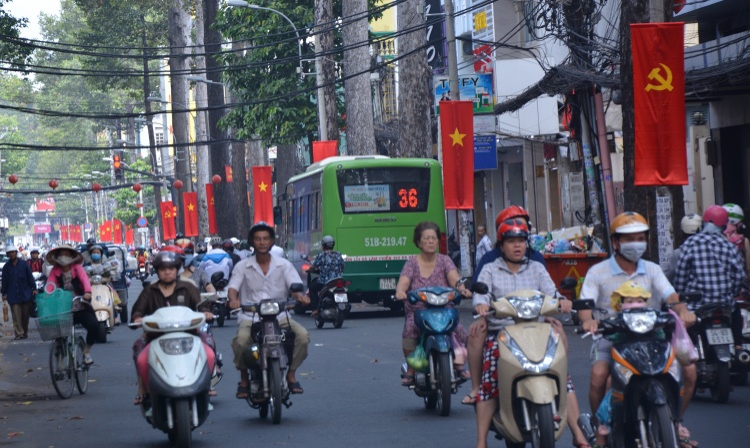 Hàng cây cổ thụ trên đường Lý Chánh Thắng (Q.3) được treo lấy cờ đỏ rực rỡ.