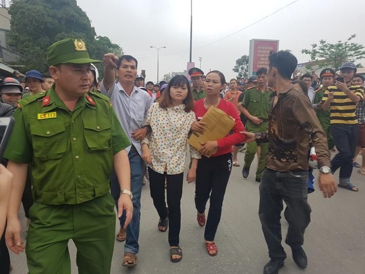 Một nữ giới (áo hoa) được người dân dìu đi sau khi lực lượng chức năng TP Thanh Hóa kiểm tra ở ngôi nhà số 744. Ảnh: Báo Giao Thông.