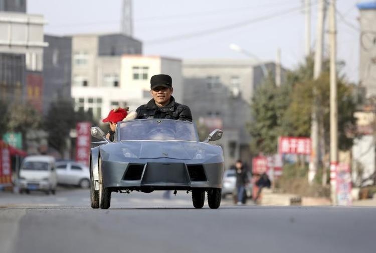 """Ông Guo, một nông dân đã bước vào tuổi 50, lái chiếc xe tự chế lấy cảm hứng từ Lamborghini cùng cháu mình trên đường phố Hồ Nam vào tháng 2 năm 2014. Ông dành 6 tháng cùng khoản """"đầu tư"""" rơi vào khoảng 821 USD để làm chiếc xe này tặng cháu."""