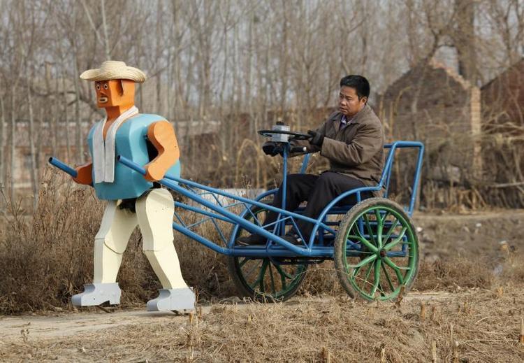 Ông Wu Yulu đang lái thử chiếc xích lô được kéo bởi một chú robot biết đi do ông phát triển tại một vùng ngoại ô Bắc Kinh. Mặc dù là một người nông dân nhưng ông Wu đam mê và bắt đầu phát triển robot từ năm 1986 từ kim loại, ốc vít hay dây điện từ một bãi rác gần đó.