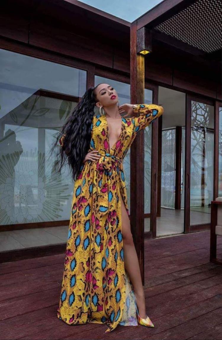 Tóc Tiên khoe trọn hình thể sexy với chiếc váy màu vàng xẻ cao in họa tiết da động vật. Cách kết hợp giày cùng tông và kiểu tóc xù cũng được cho là hoàn toàn phù hợp với tổng thể.