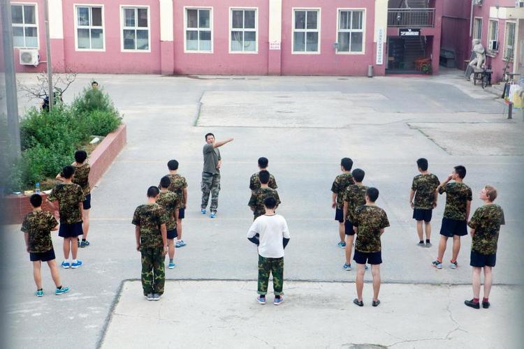 Jamie Fullerton (ngoài cùng bên phải hàng cuối cùng) nhận hướng dẫn cùng các bệnh nhân khác ngoài sân một trung tâm điều trị nghiện Internet ở Trung Quốc.