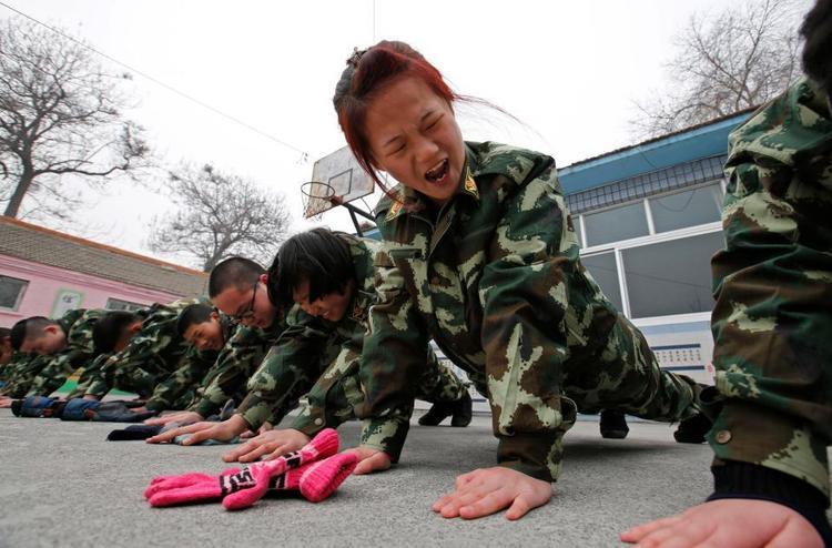 Một cô gái cau mày khi cố gắng thực hiện nốt bài chống đẩy tại Qide Education Center ở Bắc Kinh.