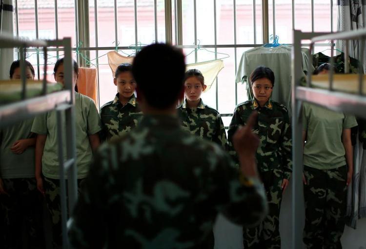 Một số học viên nữ bị bắt đứng cạnh giường để kiểm tra tại một trại cai nghiện Internet ở Trung Quốc.