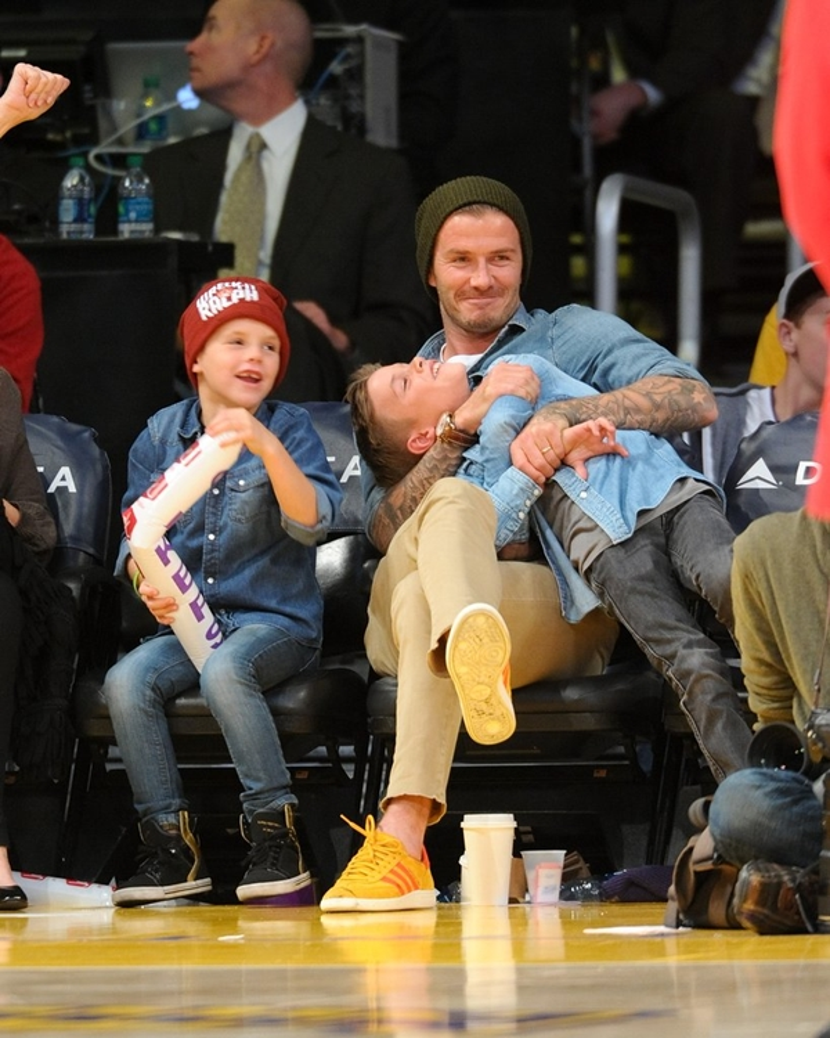 Romeo nũng nịu trong lòng bố. Hai cậu bé thường xuyên được Beckham đưa ra ngoài xem bóng.