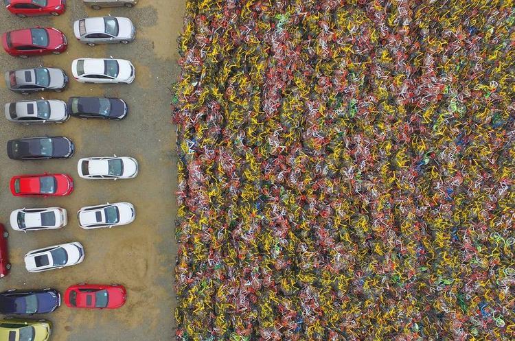 """Hàng nghìn chiếc xe đạp dùng chung bị bỏ lại đang chất đống trong bãi đỗ xe ở thành phố Nam Kinh. Chúng bị nhồi nhét trong không gian đỗ xe dài 82 m, rộng 60 m và chất thành """"núi"""" cao đến gần hai mét."""