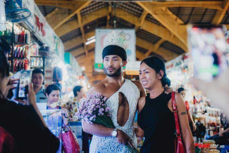 Sau đó, anh thay chiếc nón lá bằng cách đội vương miện, không ngần ngại chụp ảnh cùng những người có mặt.
