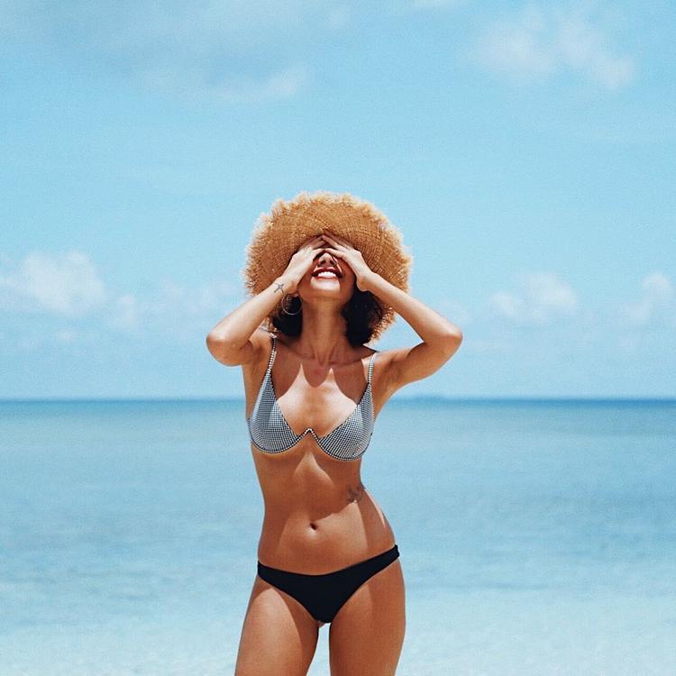 Chân dài Minh Triệu cũng chẳng hề kém cạnh với bộ bikini hai màu lạ mắt. Nàng siêu mẫu còn đội chiếc nón cói che nửa mặt để khiến vẻ ngoài thêm phần rạng rỡ.