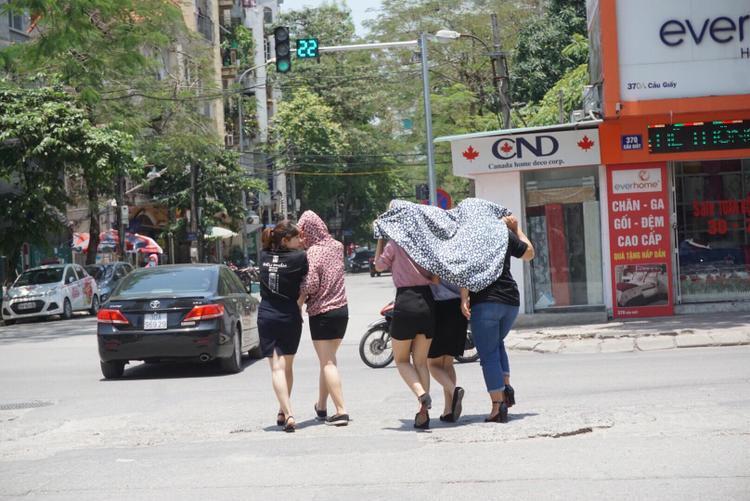 Nhóm nhân viên văn phòng vội vã đi trên đường oi nóng.