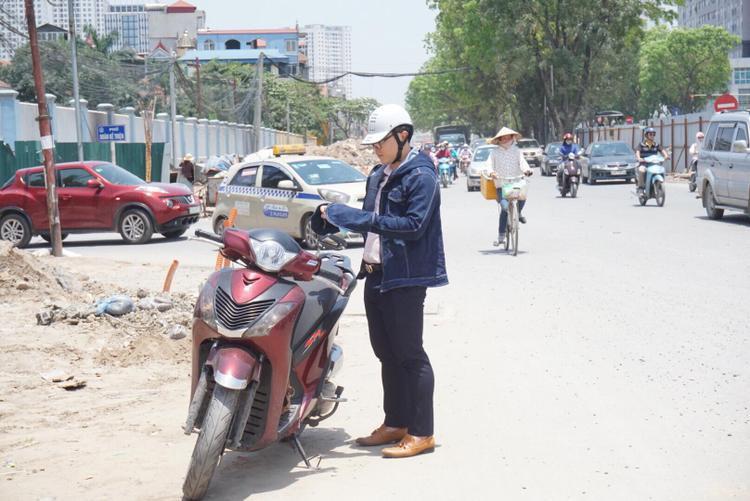 Một nam thanh niên phải dừng xe bên lề đường khoác áo để bớt nắng rát.