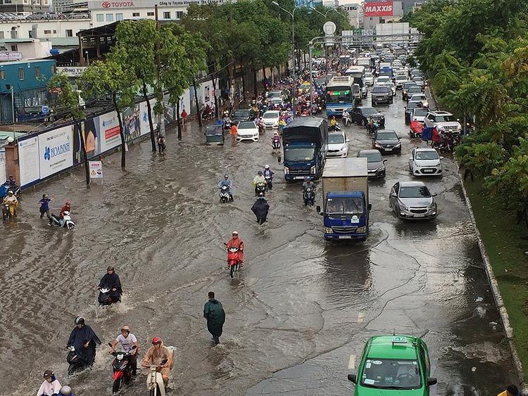 """Chiều 7-5, lúc 14g30 trời bắt đầu đổ mưa lớn trên nhiều quận huyện TP.HCM khiến nhiều tuyến đường lênh láng nước. Tại tuyến đường Nguyễn Hữu Cảnh (quận Bình Thạnh), mặc dù có """"siêu máy bơm"""" nhưng tuyến đường này ngập sâu đến nửa mét. Ảnh: N.THẮNG"""