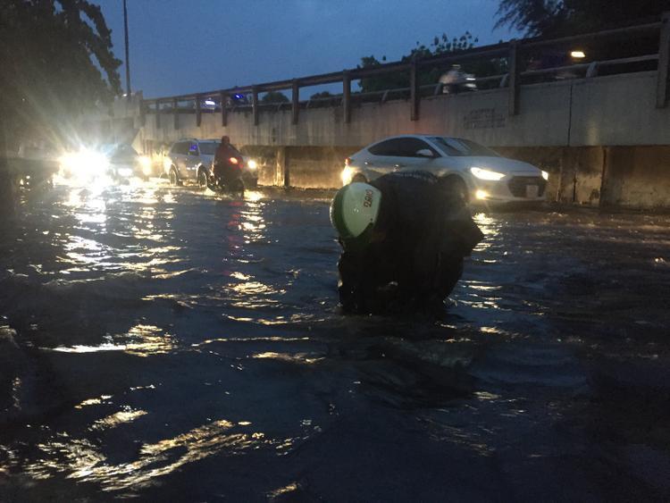 Công nhân thoát nước đô thị vớt rác tại các miệng cống trên đường Nguyễn Hữu Cảnh góp phần giúp nước rút nhanh hơn.