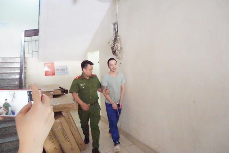 Bị cáo Tình được 1 chiến sĩ áp giải.