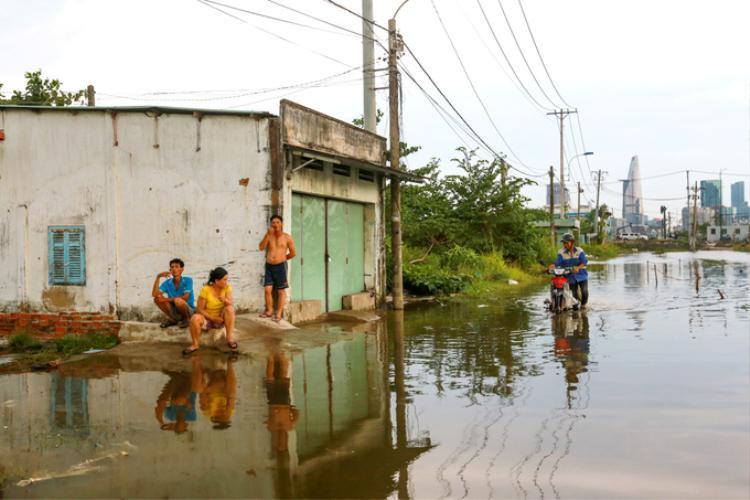 Hai bên đường Lương Định Của (quận 2, TP HCM) vẫn còn khoảng chục căn nhà tuềnh toàng của các hộ dân không di dời vì cho rằng đất của mình không nằm trong quy hoạch khu đô thị Thủ Thiêm. Con đường Lương Định Của bị chặn một đầu, lổn nhổn hạ tầng và thường xuyên bị ngập nước khi trời mưa.