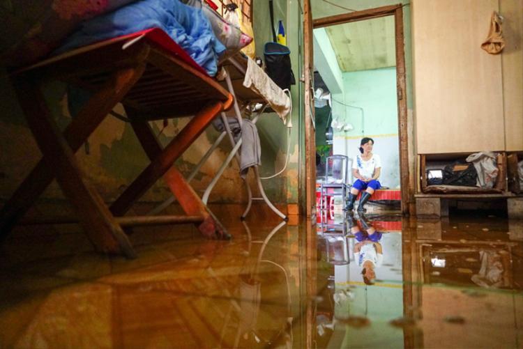 """Gần một tuần nay, những cơn mưa diễn ra thường xuyên làm nhà của bà Trịnh Thị Kim Cúc (60 tuổi) lúc nào cũng lênh láng nước. """"Nước chưa kịp rút thì cơn mưa khác ập đến. Hôm nào có triều cường thì ngập đến đầu gối luôn. Đồ đạc trong nhà tôi phải kê hết lên cao"""", bà Cúc cho biết. Khu đất của bà Cúc khoảng 5.000 m2. Năm 1997, một năm sau khi Thủ tướng phê duyệt quy hoạch Khu đô thị Thủ Thiêm, căn nhà của bà được chính quyền xác định nằm trong khu dân cư, ngoài quy hoạch. Tuy nhiên nhiều năm sau đó, ngôi nhà lại bị xác định thuộc khu vực giải tỏa. Khẳng định chính quyền làm sai, gia đình bà nhất quyết không di dời."""