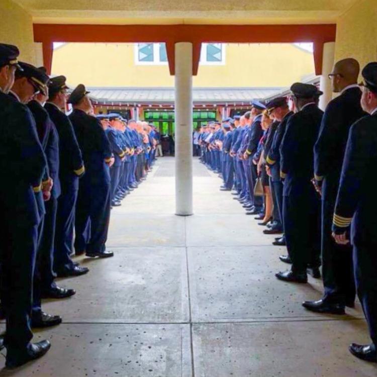 Bức ảnh này được chụp tại đám tang của Gina Rose - một nạn nhân của vụ xả súng tại Parkland, bang Florida (Mỹ). Hơn 100 phi công từ các hãng hàng không khác nhau đã đến để hỗ trợ, chia sẻ nỗi đau với cha mẹ nạn nhân và tưởng nhớ cuộc sống của cô gái trẻ xấu số. Xếp hàng ngay ngắn trong bộ đồng phục, các phi công đã trở thành ví dụ thực sự về tình đoàn kết luôn tồn tại trong xã hội chúng ta. Ảnh: Kalie Marsch/Twitter