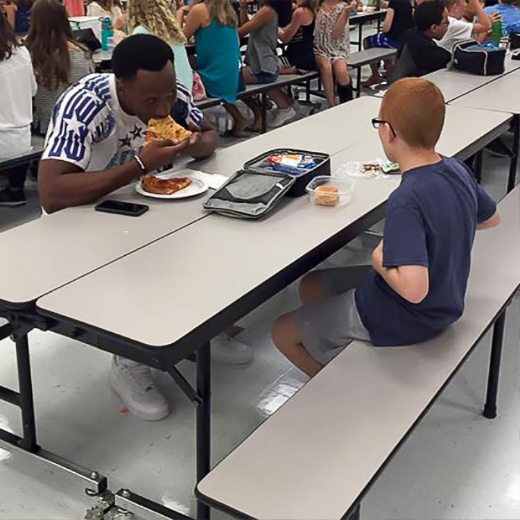 """Bức ảnh cảm động này được chính mẹ của cậu bé nhân vật chính chia sẻ. Được biết con trai cô bị bạn bè kỳ thị vì mắc chứng tự kỷ. Một người bạn đã gửi bức hình cho mẹ cậu bé với lời nhắn: """"Travis Rudolph đang ăn trưa với con trai của bạn"""". Siêu sao bóng đá và cậu bé tự kỷ đã làm quen và trò chuyện cùng nhau trong suốt bữa ăn, sau đó những cầu thủ khác đến ngồi cùng và bầu bạn với cậu bé. Mẹ cậu bé chia sẻ trên Facebook: """"Tôi không biết tại sao anh lại quyết định ăn trưa với con trai bé nhỏ của tôi nhưng chúng tôi thực sự rất biết ơn vì hành động đó và sẽ không bao giờ quên"""". Ảnh: Leah Paske/Facebook"""