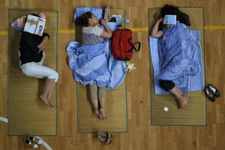 Phụ huynh tân sinh viên đưa con nhập học và ngủ trên chiếu trải trong phòng tập thể dục tại Đại học Sư phạm Hoa Trung ở Vũ Hán, tỉnh Hồ Bắc ngày 7/9/2013. Ảnh: Reuters