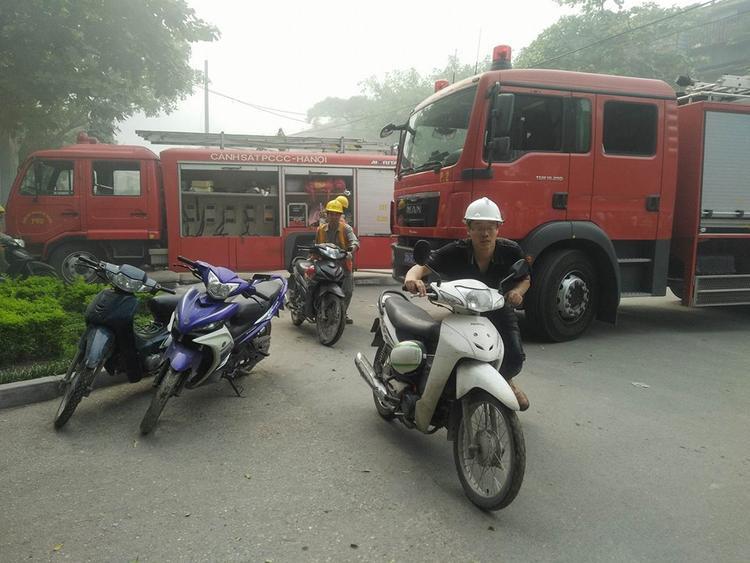 Công nhân vội đẩy xe máy ra ngoài