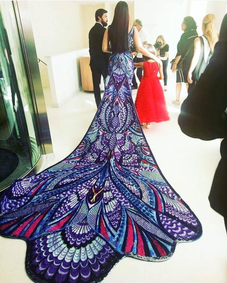 Chiếc váy được thiết kế bởi nhà mốt Michael Cinco (một nhà mốt chuyên thiết kế đầm haute couture đến từ Dubai). Thiết kế được lấy ý tưởng từ cánh bướm và hình ảnh của những chú công rực rỡ sắc màu.