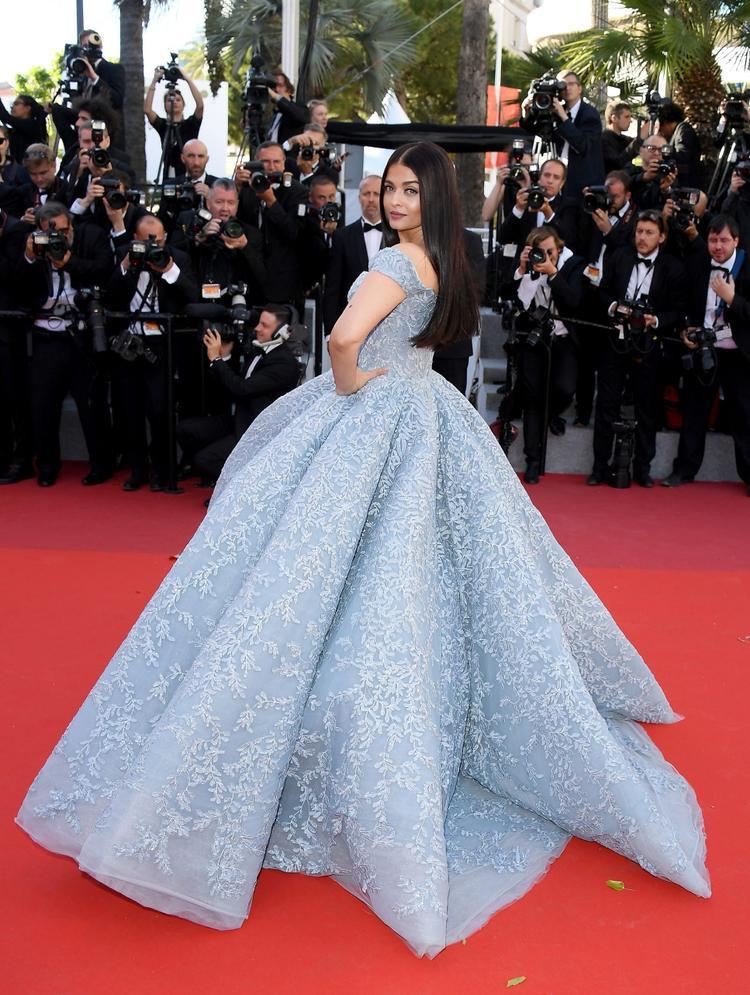 """Còn nhớ trên thảm đỏ Cannes năm ngoái, Aishwarya Rai cũng thu hút ống kính truyền thông quốc tế khi diện chiếc đầm Lọ Lem màu xanh băng tuyết quá đỗi lộng lẫy.Không chỉ tương đồng với chiếc đầm kinh điển của công chúa Lọ Lem, thiết kế này còn gợi nhớ đến chiếc đầm lấp lánh băng tuyết của nữ hoàng Elsa trong phim hoạt hình """"Frozen""""."""