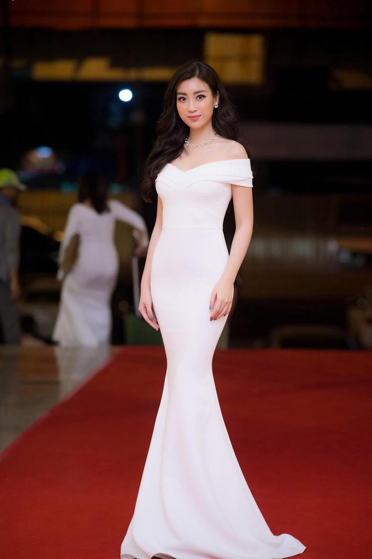 """Đỗ Mỹ Linh tiếp tục khiến cộng đồng mạng ngẩn ngơ khi lựa chọn khoe sắc cùng bộ váy đuôi cá ôm sát, gam màu trắng thanh tao. Cách mix phụ kiện tinh tế, vừa phải xứng hợp với danh xưng """"thần tiên tỷ tỷ"""" thứ 2 trong showbiz Việt."""