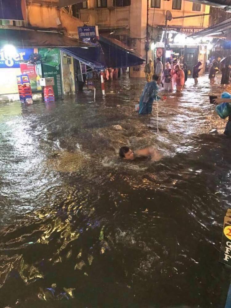 Xung quanh mọi người vẫn đang khổ sở vượt qua đoạn nước ngập.