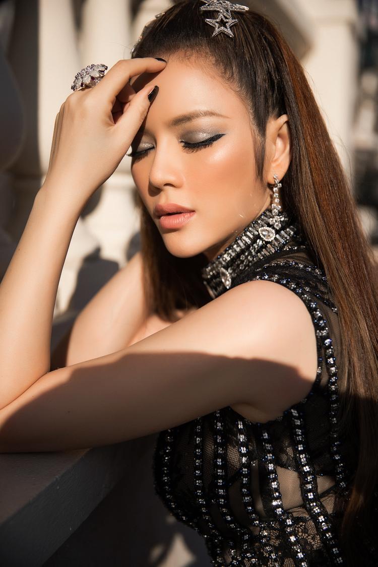 Minh Lộc tiếp tục tạo điểm nhấn vào đôi mắt với những nét kẻ đậm cùng nhũ mắt ánh bạc xuyệt tone với lớp đá đính kết trên váy.