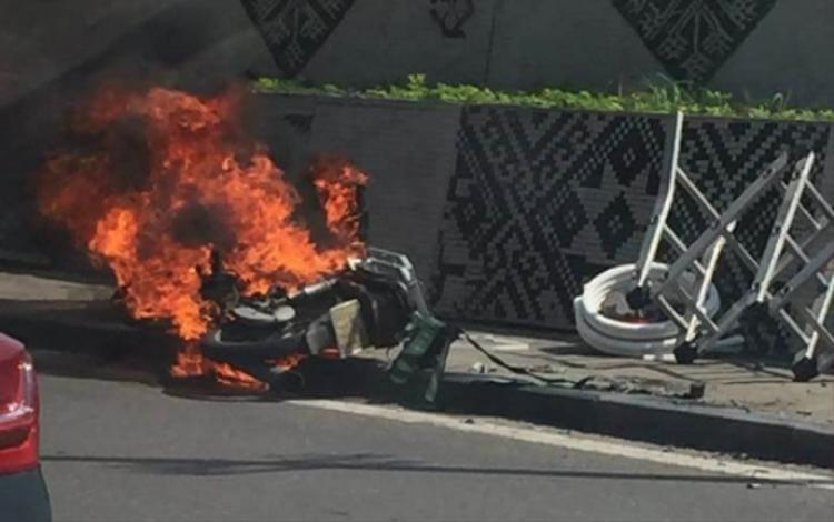 Chiếc xe máy bốc cháy dữ dội, cạnh đó là hàng hoá được tháo ra ngoài.