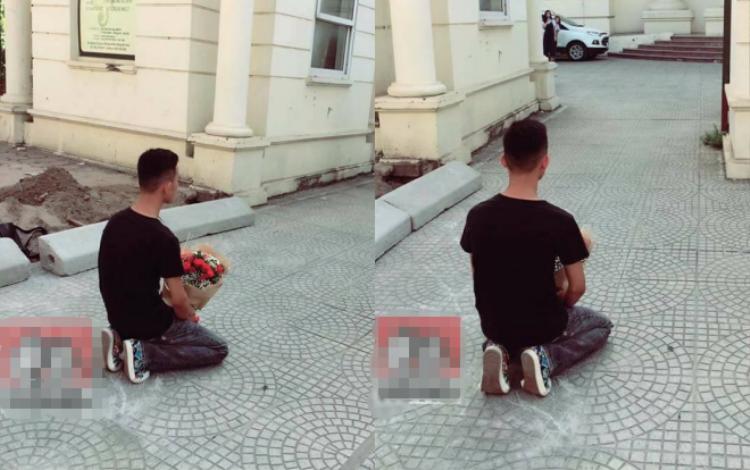 Thanh niên ôm bó hoa hồng quỳ gối trướcTrường Học viện âm nhạc Quốc Gia Việt Nam gây tranh cãi. Ảnh cắt từ clip.