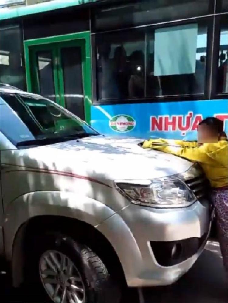 Người phụ nữ được cho là vợ của người đàn ông ngồi trong xe cùng nhân tình cố gắng đu bám trên nắp capo. Ảnh cắt từ clip.
