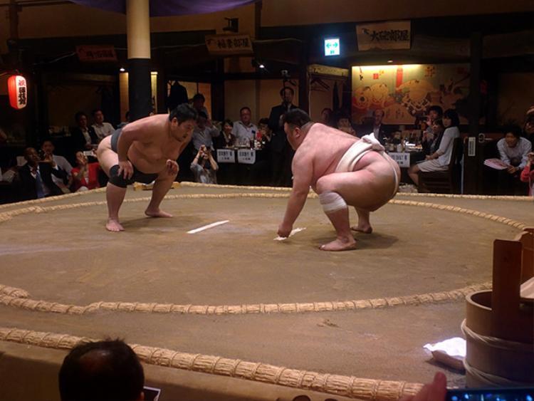 Thực khách vừa ăn vừa xem các võ sĩ thi đấu.