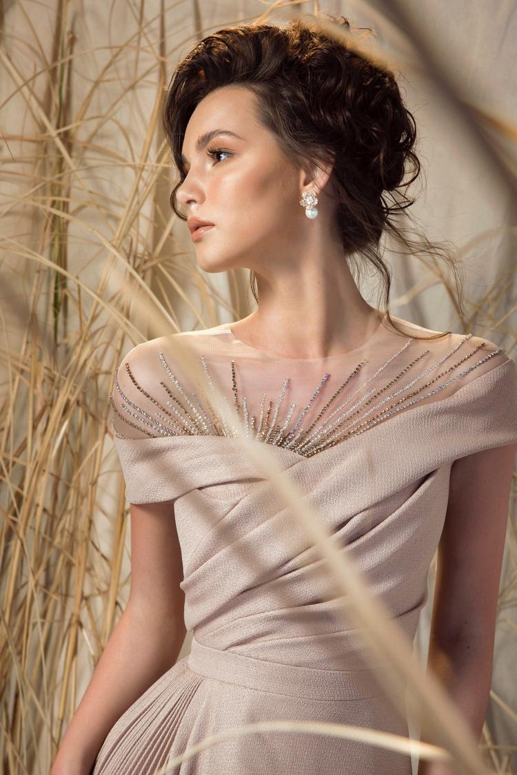 Bên cạnh đó, chất liệu cotton sợi kim tuyến cao cấp cùng điểm nhấn hình tia nắng được đính kết tỉ mỉ và kĩ thuật draping ở thân trên cũng ngay lập tức níu ánh mắt người nhìn với sự gợi cảm nhẹ nhàng.