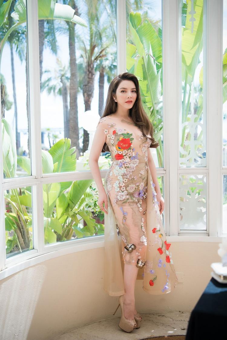 Bộ váy cách điệu với tà một bên, những bông hoa thêu xuyên suốt từ trên xuống tựa khu vườn đầy hoa thơm thu hút muôn chim và hoa bướm.