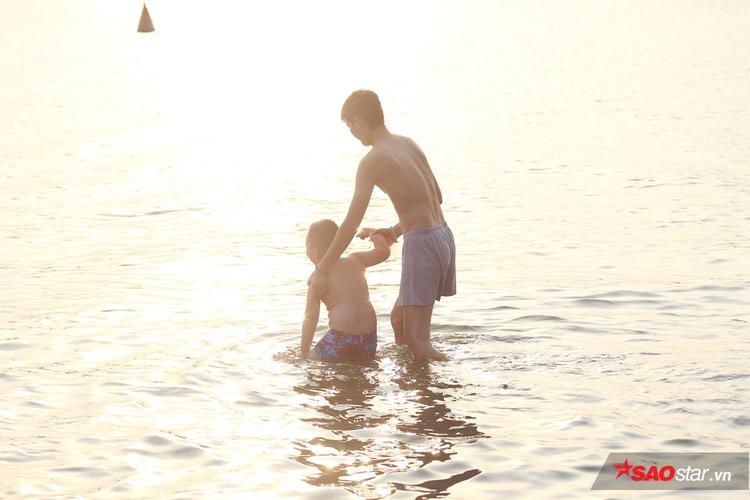 Các bậc phụ huynh vui vẻ hướng dẫn con nhỏ học bơi.