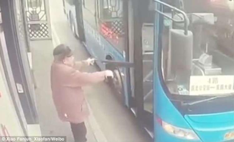 Người đàn ông dùng ô để mở cửa xe buýt sắp chuyển bánh.
