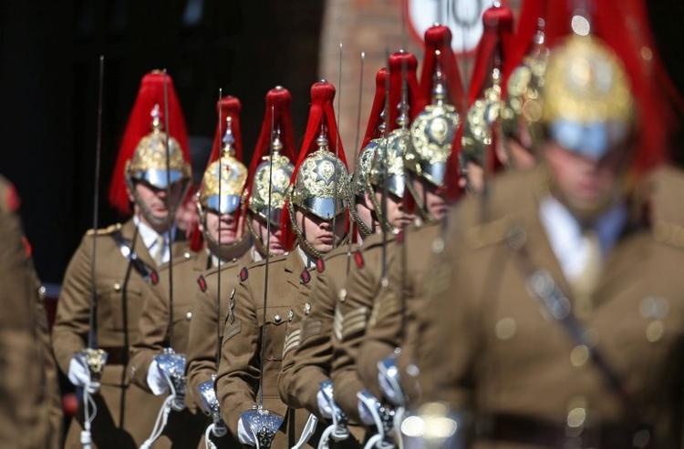 Các thành viên trong đội kỵ binh đội mũ có chóp đỏ, tay cầm gươm. Ảnh Reuters