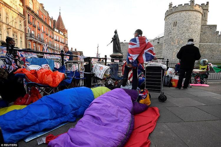 Khi vào sâu bên trong thị trấn, cảnh tượng còn đông đúc và nhộn nhịp hơn rất nhiều. Người dân mang theo chăn gối và áo ấm, ngủ qua đêm trên lề đường để chờ đám cưới hoàng gia. Ảnh Reuters